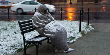 A homeless man sits covered in snow early on March 25, 2013 in Washington, DC. A messy Monday is in store for millions along the East Coast, with winter weather advisories warning of a mixture of snow and rain for Washington, DC, Philadelphia, metropolitan New York and parts of northeast New Jersey. AFP PHOTO / Karen BLEIER (Photo credit should read KAREN BLEIER/AFP/Getty Images)